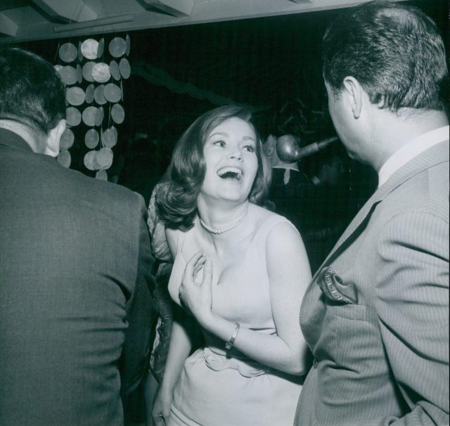 Quinn O'Hara smiling at Cy Howard at the party. 1965
